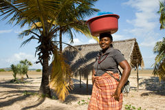 Woman has different goods in a bowl and carries it on her head traditionally. Royalty Free Stock Image