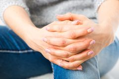Woman has folded hands over the knees. Young woman has folded hands over the knees - closeup royalty free stock photo