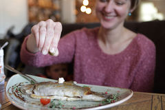 Woman has fried trout Stock Photos