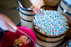 A woman has a handfull of blue salt water taffy in a store Stock Images