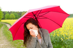 Woman has hay fever. Young woman with red umbrella  has hay fever Stock Photo