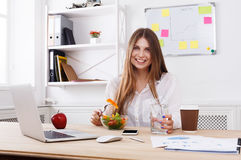 Woman has healthy business lunch in modern office interior Royalty Free Stock Photos