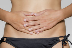 Woman has her hands on her stomach Stock Images