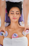 Woman has herbal ball massage in ayurveda spa wellness center. Herbal ball massage in ayurvedic spa. Female massagist with young woman in wellness center stock photography