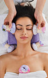 Woman has herbal ball massage in ayurveda spa wellness center. Herbal ball face massage in ayurveda spa. Female massagist with young woman in wellness center royalty free stock images