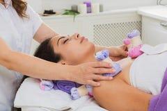 Woman has herbal ball massage in ayurveda spa wellness center royalty free stock photo