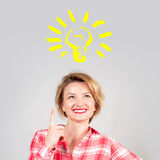 Woman has an idea, showing finger up on light bulb Royalty Free Stock Photography