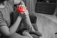 Woman has knee pain, black and white photo red accent, close up of pain stock photography