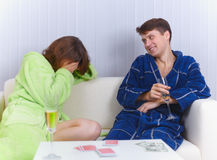 Woman has lost in cards to man and cries Royalty Free Stock Photos