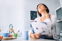 Woman has a neck pain when reads a magazine on the kitchen at mo royalty free stock image