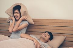 A woman has a nuisance to the man he loves sleeping loud snoring. A women has a nuisance to the men he loves sleeping loud snoring.Concept of life together stock images