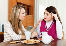 Woman has problem, girlfriend consoling her. Crying brunette women has problem, girlfriend consoling her at table royalty free stock image