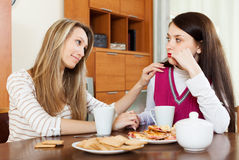 Woman has problem, girlfriend consoling her. Crying brunette women has problem, girlfriend consoling her at table in home stock image