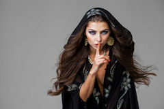 Woman has put forefinger to lips as sign of silence. Young beautiful brunette woman has put forefinger to lips as sign of silence royalty free stock images