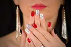THE WOMAN HAS RED,black,glittering silver and white nails with heart.She holds her palms in front of her face. She has red lips. Woman with extravagant earrings royalty free stock image