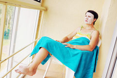Woman has a rest with a cosmetic mask on her face Royalty Free Stock Photos