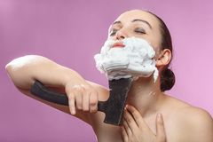 Woman has shave. Beautiful woman with shaving cream on pink background has shave with hatchet stock photo