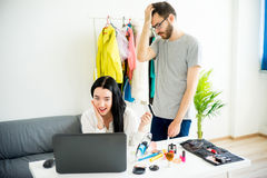 Woman has a shopping addiction. Woman is overspending money online and her frustrated husband telling her that Stock Photography
