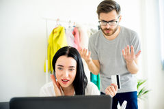 Woman has a shopping addiction. Woman is overspending money online and her frustrated husband telling her that Stock Photo