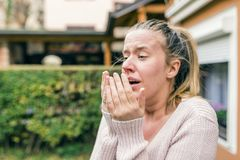 Woman has sneezing. Young woman is having flu and she is sneezin Stock Images