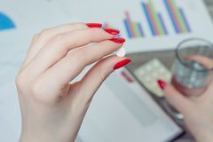 Woman has to work in spite of being ill. Close up photo of woman. `s hand holding a pill royalty free stock photography