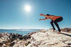 Woman has yoga practice on the deserted sea coast Stock Photos