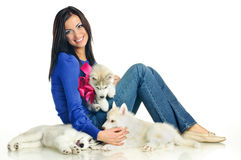Woman and haski. Playing woman with puppies of siberian haski on white background Royalty Free Stock Photo