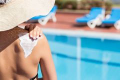 Woman in hat is applying sun cream on her shoulder by the pool. Sun Protection Factor in vacation, concept.  stock images