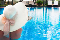 Woman  with hat  from back in  swimming pool Stock Photos