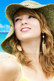 Woman with hat at the beach. Portrait of a beautiful young blond woman on vacations at the beach with large straw sun hat Stock Photography