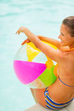 Woman in hat with beach ball sitting at poolside Royalty Free Stock Photo