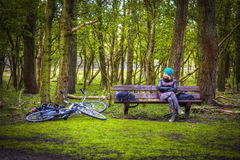 Woman in a hat with a bike sitting in the park Stock Photos
