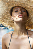 Woman in hat and black stylish swimsuit poses near Royalty Free Stock Images