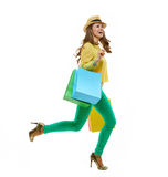 Woman in hat and bright clothes with shopping bags running Royalty Free Stock Images