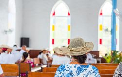 Woman in a hat in a catholic church in the service, Rarotonga, Aitutaki, Cook Islands. With selective focus. Back view.  royalty free stock photos