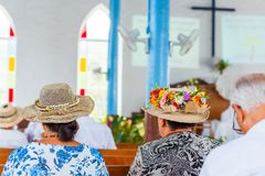 Woman in a hat in a catholic church in the service, Rarotonga, Aitutaki, Cook Islands. With selective focus. Back view.  stock photos