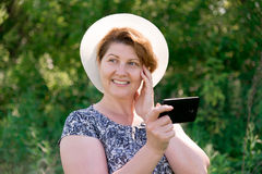 Woman in hat with cell phone outside Stock Photography