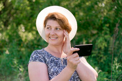 Woman in hat with cell phone outside Stock Photos