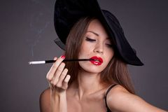 Woman in hat with cigarette Stock Images