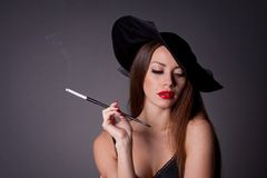 Woman in hat with cigarette. Beautiful elegant woman in hat with cigarette Royalty Free Stock Photo