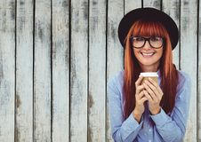 Woman in hat with coffee cup against wood panel Stock Photos