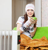 Woman in hat with cup near warm radiator Stock Photo