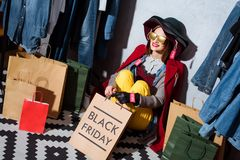 woman in hat and different clothes with sale tags sitting in boutique with shopping bags and clothes around stock image