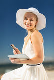 Woman in hat doing online shopping outdoors Stock Images