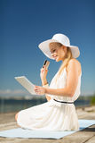Woman in hat doing online shopping outdoors Stock Photos