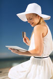 Woman in hat doing online shopping outdoors Royalty Free Stock Images