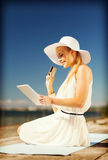 Woman in hat doing online shopping outdoors Royalty Free Stock Image