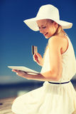 Woman in hat doing online shopping outdoors Stock Image