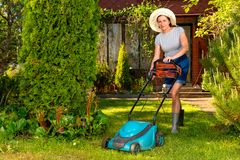 Woman in hat with electric lawn mower on garden background Stock Image