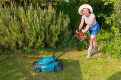 Woman in hat with electric lawn mower on garden background Stock Images
